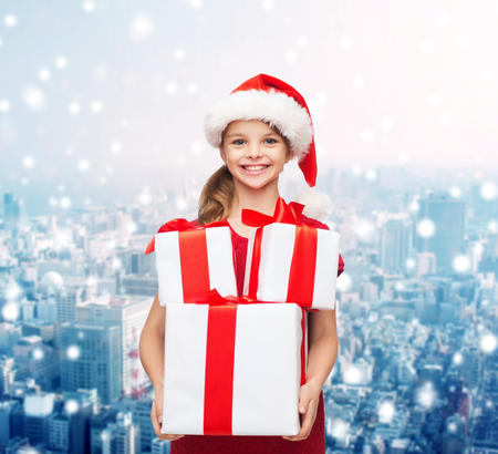 holidays, presents, christmas, childhood and people concept - smiling little girl in santa helper hat with gift boxes over snowy city background photo