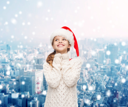 christmas, holidays, childhood and people concept - smiling girl in santa helper hat over snowy city background photo