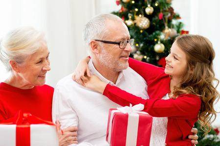 cajas navide�as: familia, d�as de fiesta, la generaci�n, la Navidad y la gente concepto - abuelos y nieta sonriente con cajas de regalo sentado en el sof� en casa