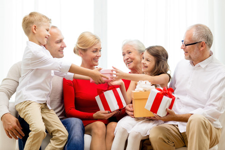 three gift boxes: family, holidays, generation, christmas and people concept - smiling family with gift boxes sitting on couch at home