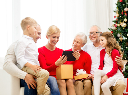 three generations: family, holidays, christmas, technology and people concept - smiling family with gift box and tablet pc computer sitting on couch at home