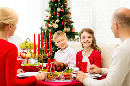 family, holidays, generation, christmas and people concept - smiling family having dinner at home photo