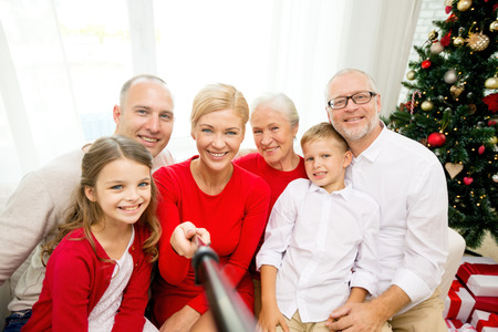 family, holidays, generation, christmas and people concept - smiling family with camera and selfie stick making picture at home photo