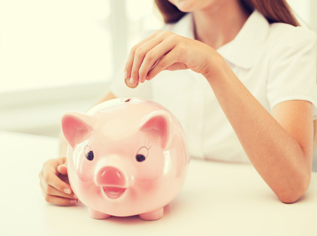 education, school and money saving concept - smiling child putting coin into big piggy bank Stock Photo