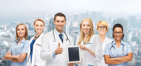medicine, technology and healthcare concept - team or group of doctors and nurses with tablet pc computer blank screen showing thumbs up photo
