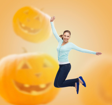 flying woman: happiness, freedom, holidays and people concept - smiling young woman jumping in air over halloween pumpkins background