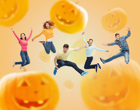 happiness, freedom, holidays and people concept - group of smiling teenagers jumping in air over halloween pumpkins background photo