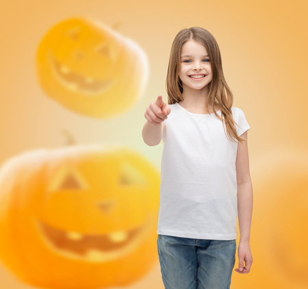 holidays, childhood, happiness, gesture and people concept - smiling little girl in white blank shirt pointing finger at you over halloween pumpkins background photo