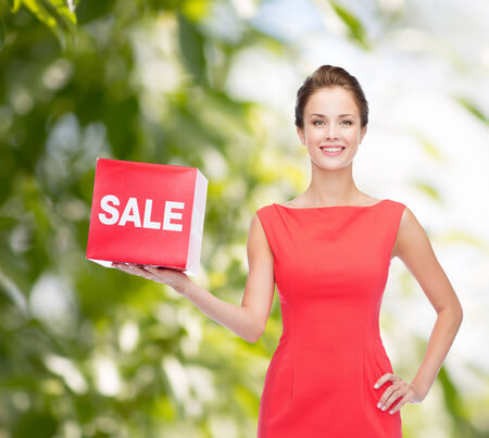 shopping, gifts, christmas and holiday concept - smiling young woman in dress with red sale sign photo