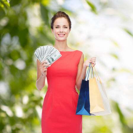 woman holding money: shopping, sale, christmas and holiday concept - smiling elegant woman in red dress with shopping bags and dollars