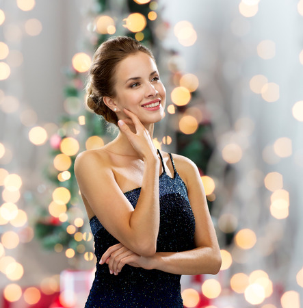 people, holidays, and glamour concept - smiling woman in evening dress showing earrings over christmas tree and lights background photo