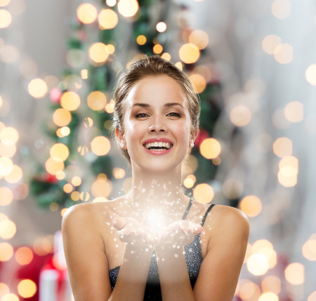 wealth: people, holidays and magic concept - laughing woman in evening dress holding something over christmas tree and lights background