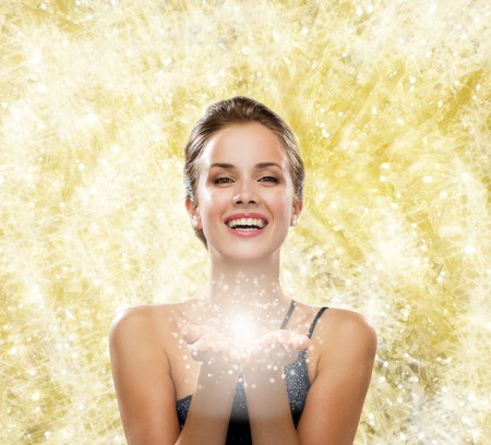 something: people, holidays, christmas and magic concept - laughing woman in evening dress holding something over yellow lights background