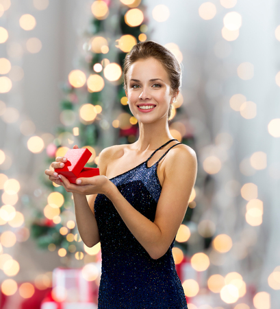 fancy box: holidays, celebration and people concept - smiling woman in evening dress with small red gift box over christmas tree and lights background