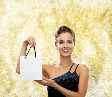 holydays: christmas, sale, advertisement, holydays and people concept - smiling woman with white blank shopping bag over yellow lights background