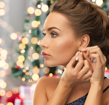 glamour: people, holidays and glamour concept - close up of beautiful woman wearing earrings over christmas tree and lights background