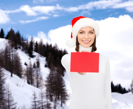 christmas, holdays, people, advertisement and sale concept - happy woman in santa helper hat with blank red card over snowy mountains background photo