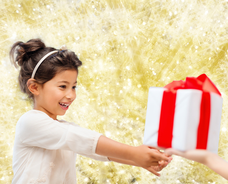 holidays, presents, christmas, childhood and people concept - smiling little girl with gift box over yellow lights background photo