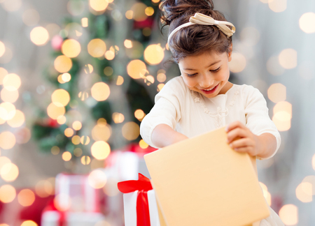 holidays, presents, childhood and people concept - smiling little girl with gift box over living room and christmas thee background