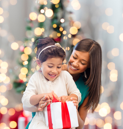 holidays, celebration, family and people concept - happy mother and little girl with gift box over living room and christmas tree background
