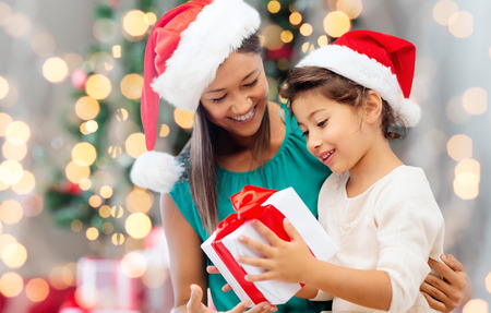 holidays, celebration, family and people concept - happy mother and little girl in santa helper hats with gift box over living room and christmas tree background