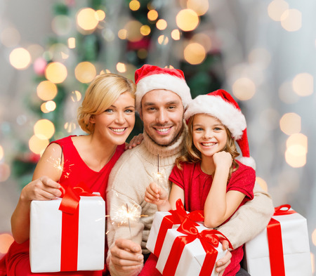 christmas, holidays,  family and people concept - happy mother, father and little girl in santa helper hats with gift boxes over living room and christmas tree background photo