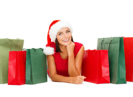 sale, christmas, x-mas concept - smiling woman in red shirt and santa helper hat with shopping bags