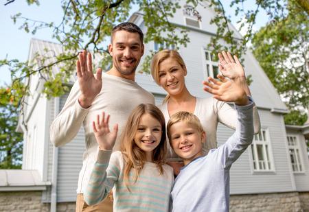 casita de dulces: la familia, la generación, el hogar, el gesto y la gente concepto - familia feliz de pie delante de la casa agitando las manos al aire libre Foto de archivo