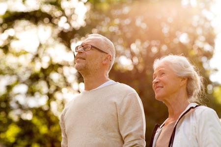 parejas caminando: familiar, la edad, el turismo, los viajes y el concepto de la gente - pareja de ancianos en el parque