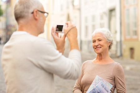 parejas caminando: la edad, el turismo, los viajes, la tecnología y la gente concepto - pareja de alto nivel con el mapa y cámara de fotografiar en la calle