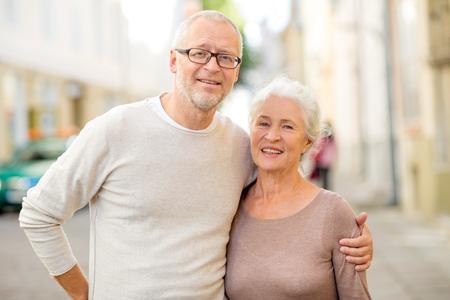Familie, leeftijd, toerisme, reis en mensenconcept - senior paar knuffelen op stadsstraat