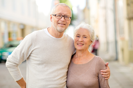 family, age, tourism, travel and people concept - senior\ couple hugging on city street