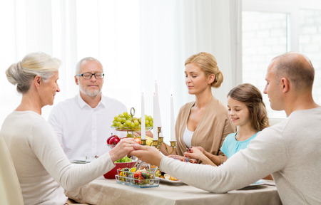 familia orando: concepto de familia, días de fiesta, la generación y la gente - sonriendo familia cenando y orando en casa Foto de archivo