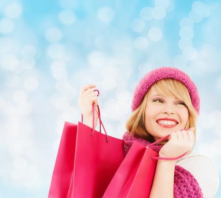 幸福、冬の休日、クリスマス、人々 の概念 - 青いライトの背景の上の帽子とスカーフ ピンクの買い物袋を若い女性を笑顔 写真素材
