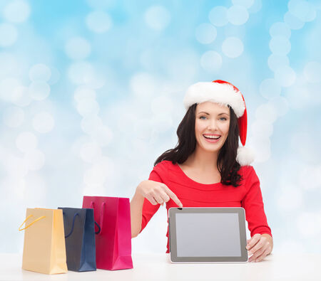 christmas, holidays, technology, advertising and people concept - smiling woman in santa helper hat with shopping bags and tablet pc computer over blue lights background photo