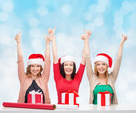christmas, holidays, celebration, decoration and people concept - smiling women in santa helper hats with decorating paper and gift boxes showing thumbs up over blue lights background photo