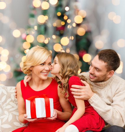 christmas room: christmas, holidays, family and people concept - happy mother, father and little girl with gift box kissing over living room and christmas tree background