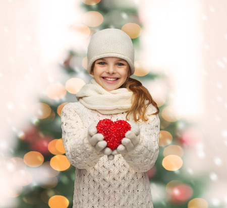 holidays, happiness, charity concept - smiling teenage girl in winter clothes with small red heart photo