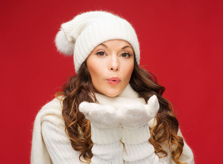 christmas, xmas, people, happiness concept - happy woman in winter clothes blowing on palms photo