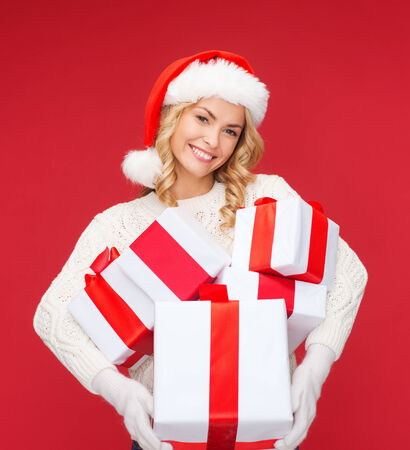 christmas, xmas, winter, happiness concept - smiling woman in santa helper hat with many gift boxes photo