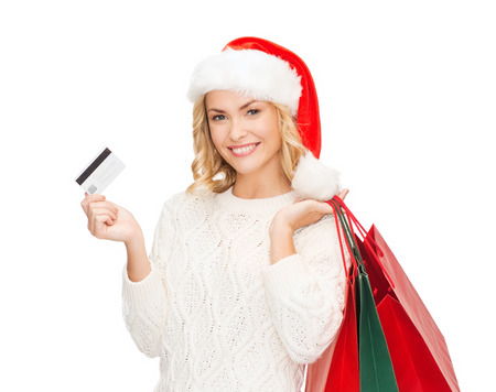 sale, gifts, christmas, xmas concept - smiling woman in santa helper hat with shopping bags and credit card photo