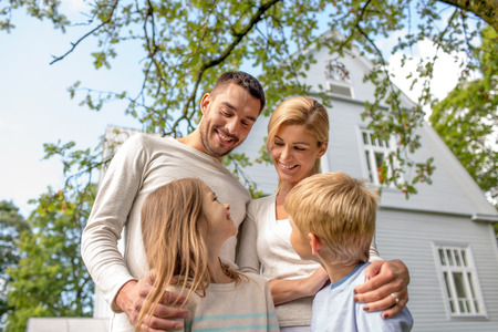 home family: family, happiness, generation, home and people concept - happy family standing in front of house outdoors Stock Photo