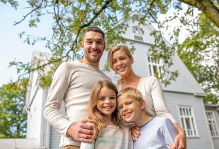 familias jovenes: la familia, la felicidad, la generaci�n, el hogar y las personas concepto - la familia feliz que se coloca delante de la casa al aire libre Foto de archivo