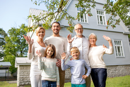 family, generation, gesture, home and people concept - happy family standing in front of house waving hands outdoors photo