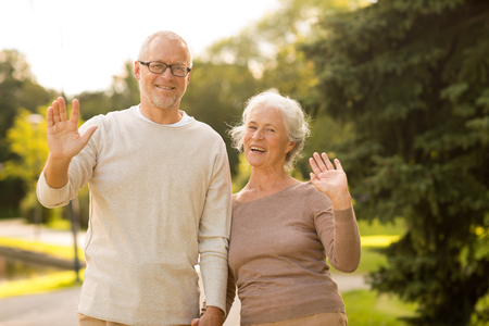 family, age, tourism, gesture and people concept - senior couple waving hands in city park photo