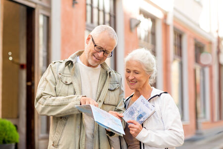 family, age, tourism, travel and people concept - senior\ couple with map and city guide on street