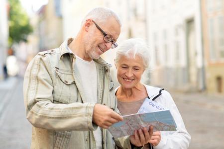 familie, leeftijd, toerisme, reizen en mensen concept - senior paar met kaart en stadsgids op straat
