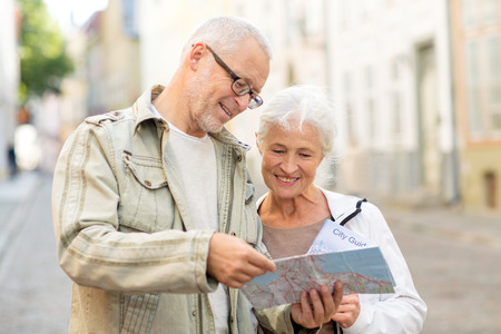 nice looking: family, age, tourism, travel and people concept - senior couple with map and city guide on street