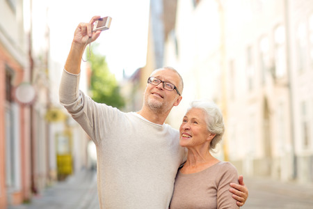 age, tourism, travel, technology and people concept - senior couple with camera taking selfie on street photo