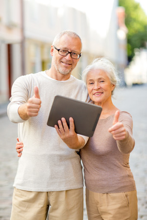 age, tourism, travel, technology and people concept - senior couple with tablet pc computer showing thumbs up gesture on street photo